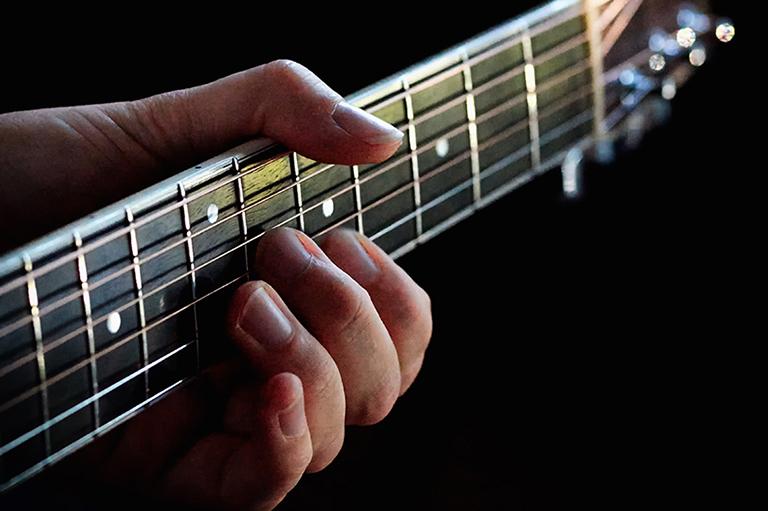 Detail eines Gitarrenhalses und einer Hand